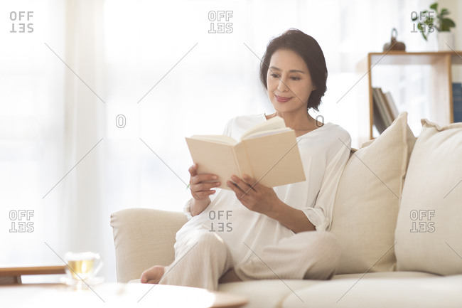 Mature Chinese woman reading book on sofa