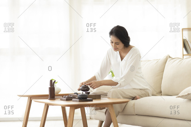 Mature Chinese woman drinking tea in living room