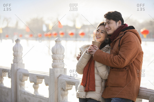 Happy young Chinese couple dating outdoors in winter