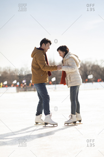 Happy young Chinese couple ice skating outdoors