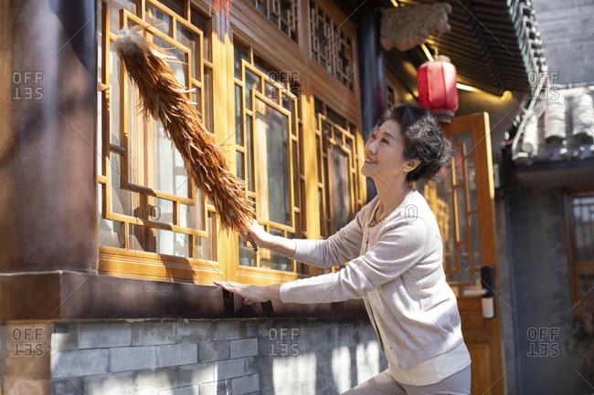 Happy Chinese senior woman dusting