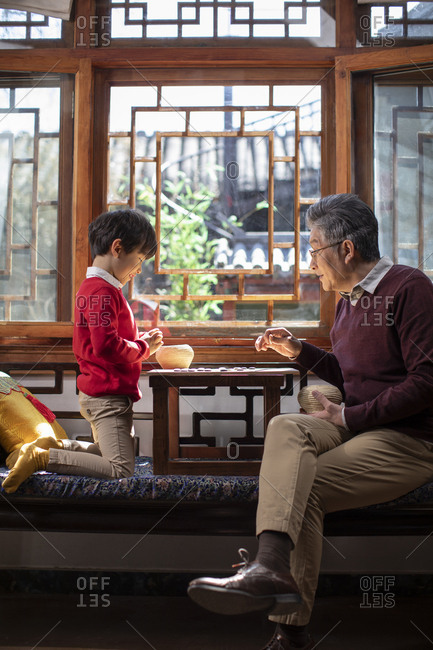Happy Chinese grandfather and grandson playing the game of go