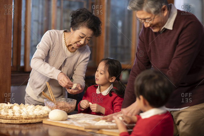 Happy Chinese family making dumplings
