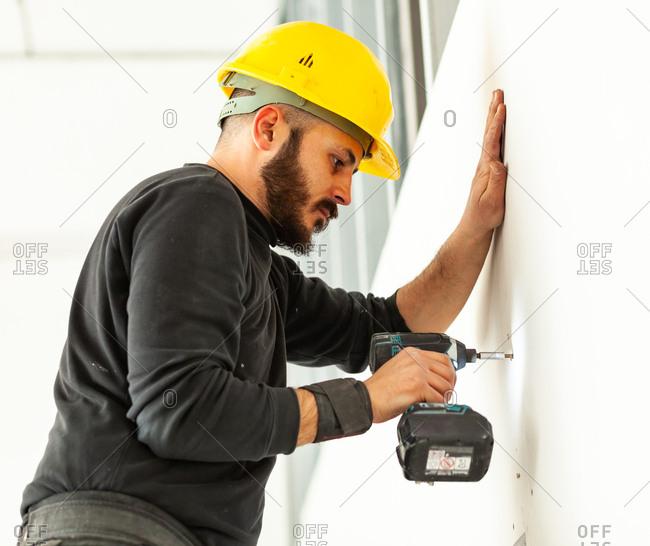 Worker screws plasterboard panels