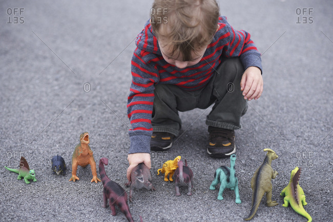 High angle view of boy playing with dinosaur figurines while crouching on road