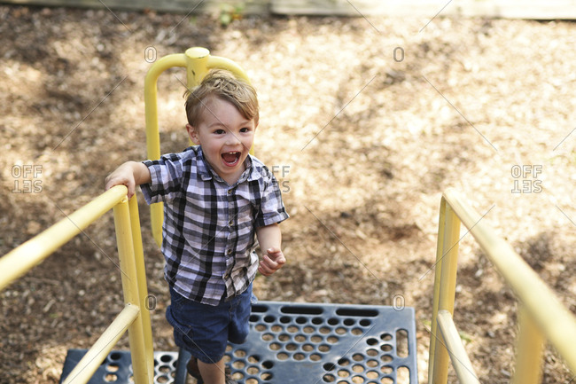 High angle view of playful boy shouting while standing on outdoor play equipment at playground