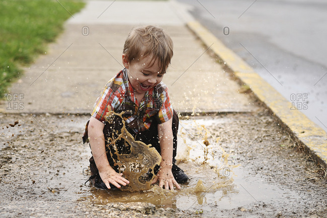 Playful boy playing in puddle on footpath