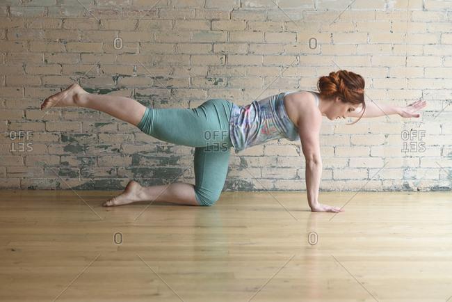 Side view of woman dancing on hardwood floor in studio