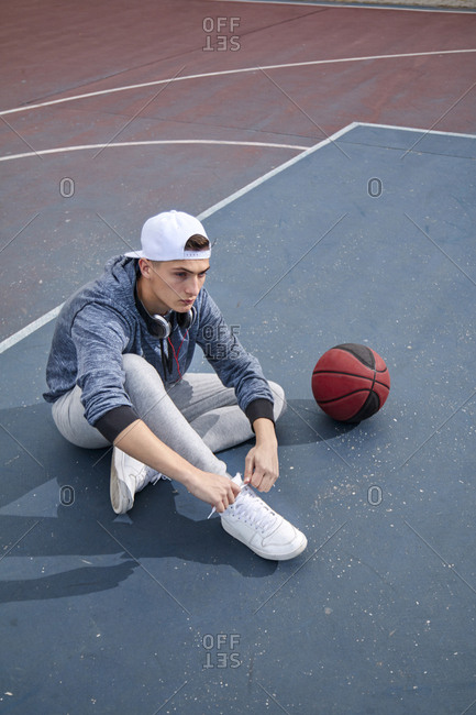 High angle view of teenage boy tying shoelace while sitting at basketball court