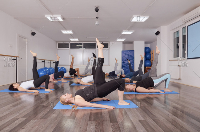 Group of people lying on exercise mats while exercising in pilates class