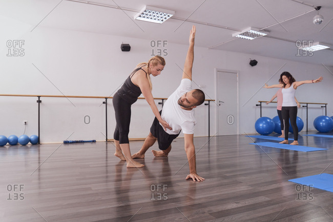 Yoga instructor teaching posture to man exercising in pilates class