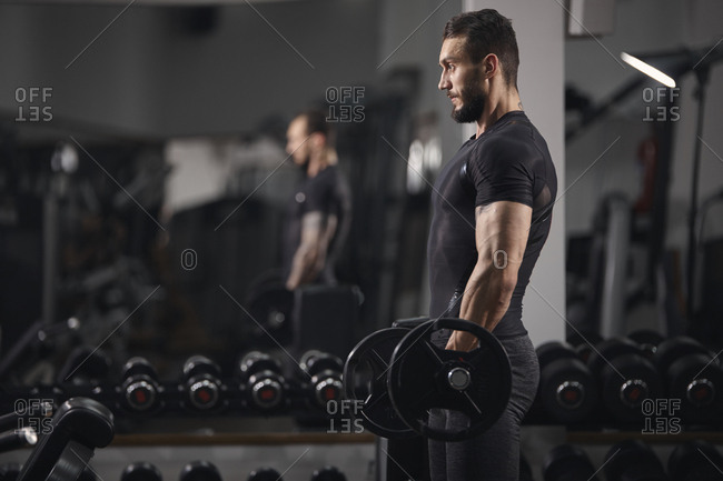 Side view of man lifting barbell while exercising at gym