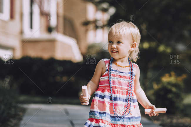 Cute baby girl wearing necklaces while holding chalks at footpath