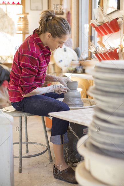 Adult woman shaping a piece of pottery on a wheel in her studio