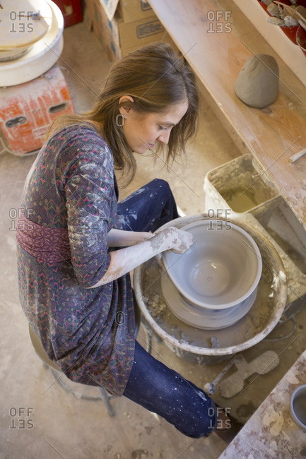 Above perspective of woman shaping a bowl on a potter's wheel