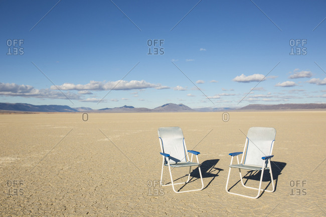 Two chairs in the middle of wide open desert