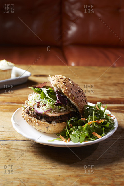 Close-up of burger with arugula served in plate on wooden table