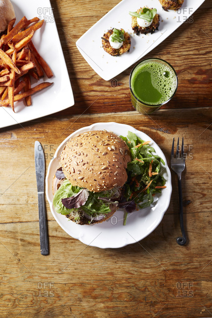 High angle view of burger with arugula served in plate by juice and french fries on wooden table