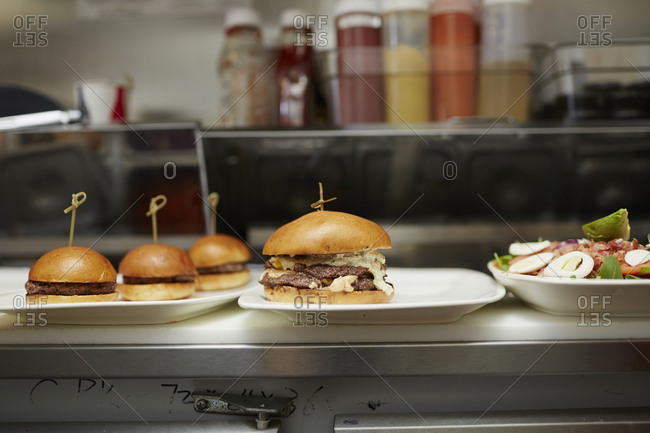 Burgers served in plates on kitchen counter