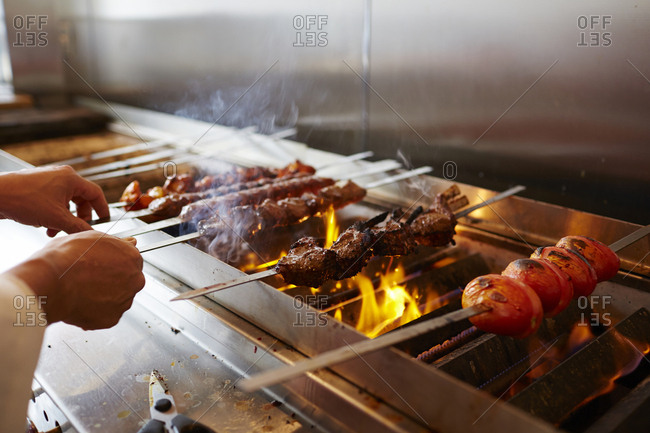 Cropped hands of chef making kebab on barbecue grill in commercial kitchen