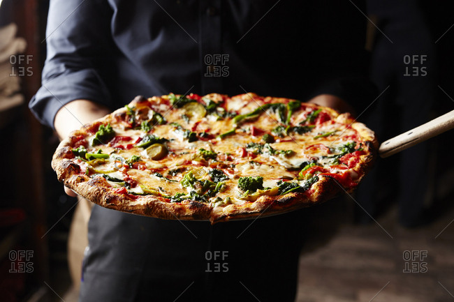 Midsection of man holding pizza
