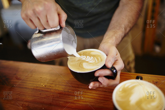 Midsection of barista making frothy drink at cafe