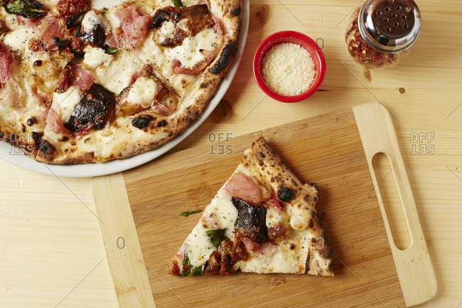 Overhead view of pizza slice on wooden cutting board