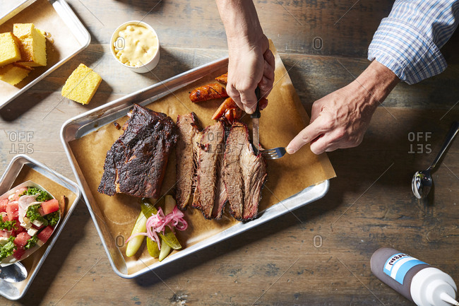 Cropped hands of man using cutlery while cutting roasted meat on table