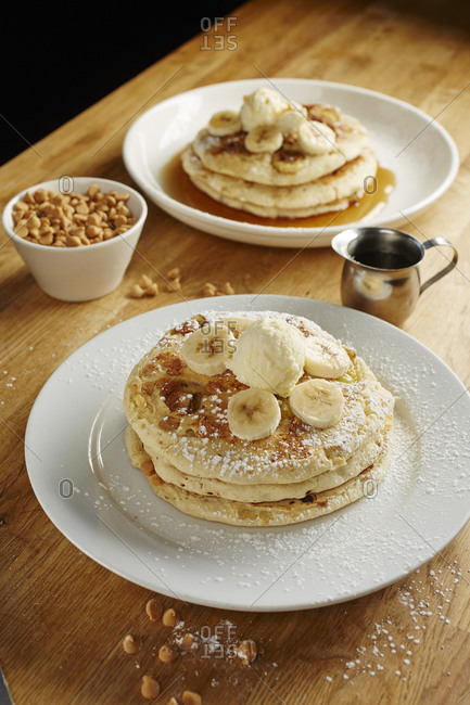 Close-up of pancakes served with banana slices in plate on table