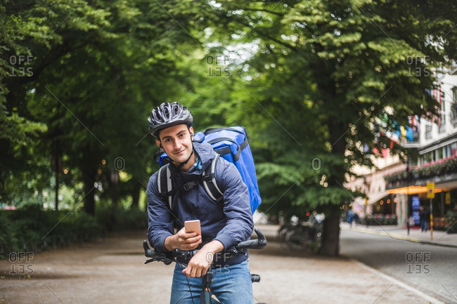 Portrait of confident food delivery man with bicycle in city