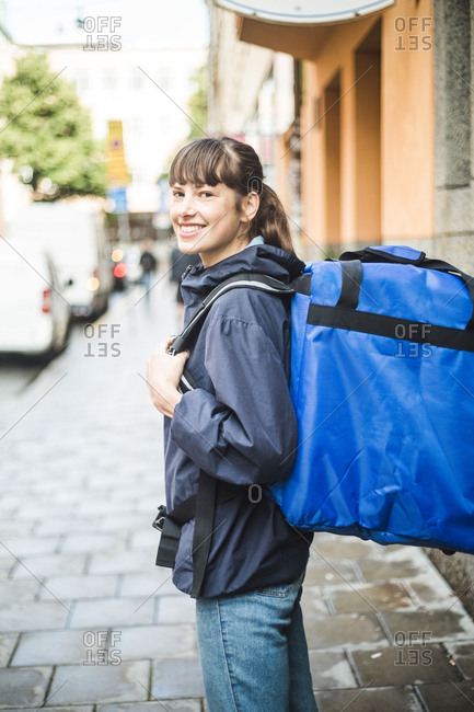 Portrait of confident delivery woman with bag standing on sidewalk