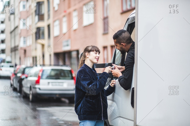 Young woman signing on smart phone being held by male mover in truck