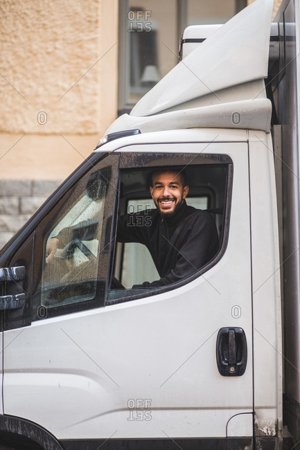Portrait of smiling male mover driving truck