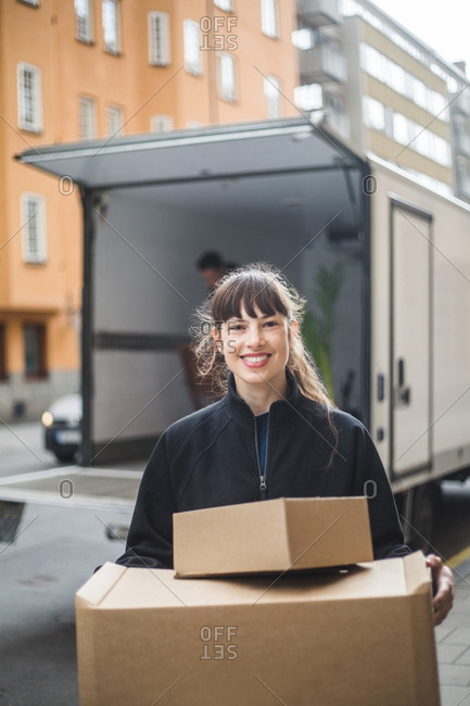 Portrait of smiling female mover carrying cardboard boxes