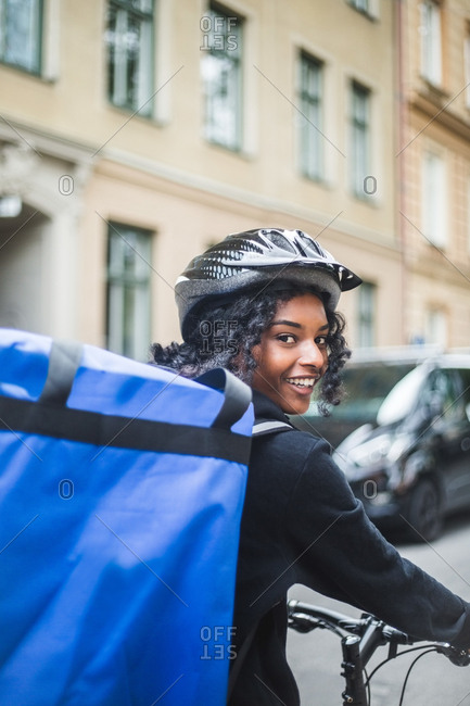 Portrait of smiling delivery woman with bag in city