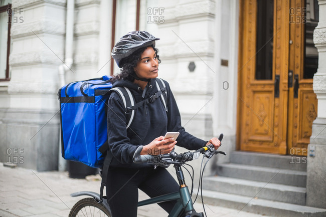 Food delivery woman looking away while holding smart phone in city