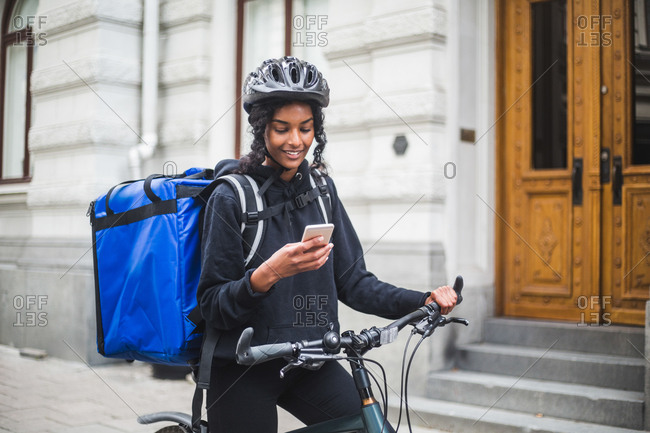 Food delivery woman using smart phone in city