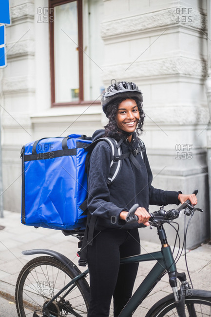 Portrait of smiling delivery woman with bicycle in city