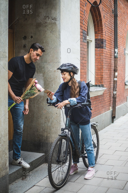 Delivery woman showing mobile phone to male customer while delivering bouquet