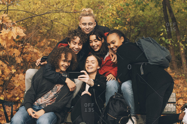 Teenage girl taking selfie with friends while sitting on bench against trees during autumn