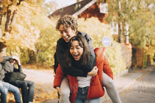 Cheerful teenage girl piggybacking male friend outdoors
