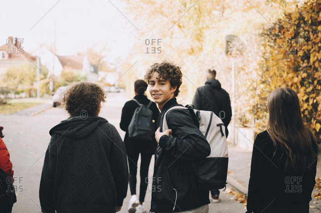 Portrait of smiling teenage boy carrying backpack while walking with friends on street in city
