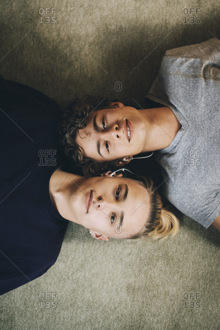 Directly above portrait of teenage boys lying together on carpet at home
