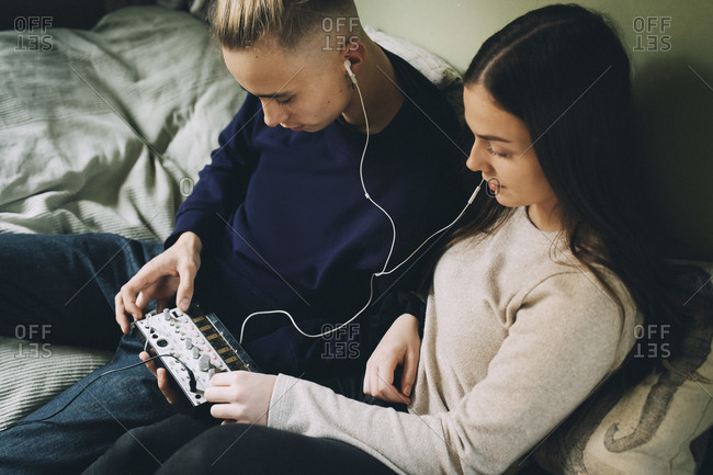 High angle view of teenage friends using sound mixer at bedroom