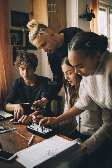Teenage friends using audio equipment while doing homework at home