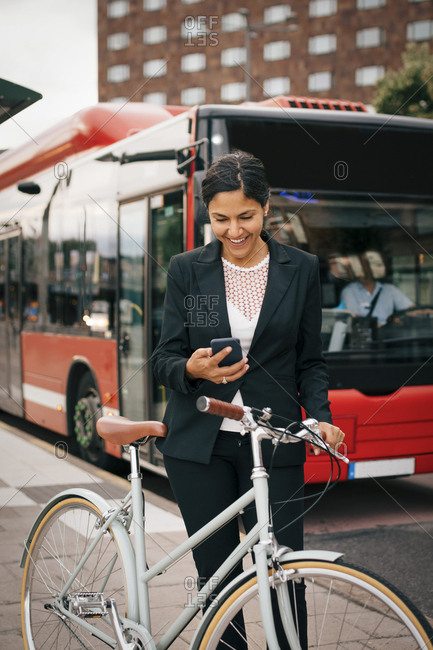 Smiling businesswoman using smart phone while standing with bicycle against bus on street in city