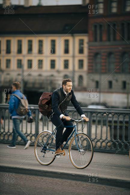 Full length of businessman riding bicycle on bridge