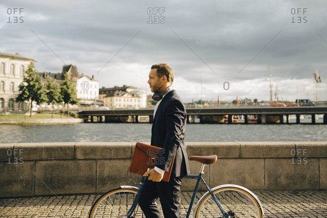 Side view of businessman walking with bicycle on footpath in city against sky