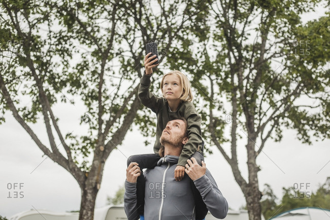 Girl holding mobile phone while sitting on father's shoulders against trees