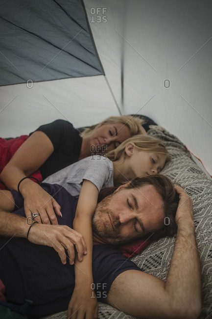 Family sleeping with closed eyes in tent during camping